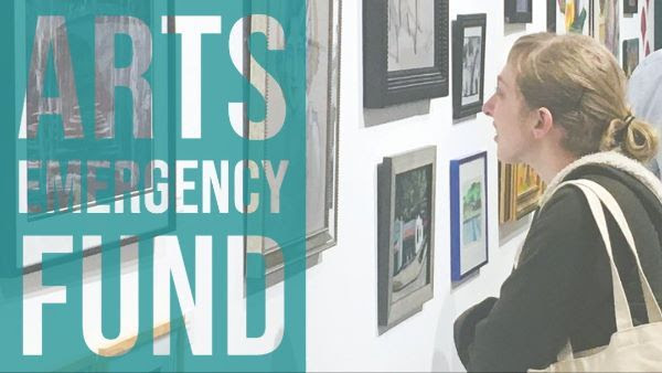 Arts Emergency words over woman looking at painting
